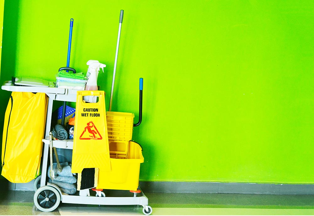 A cleaning cart sits parked against a lime green wall.