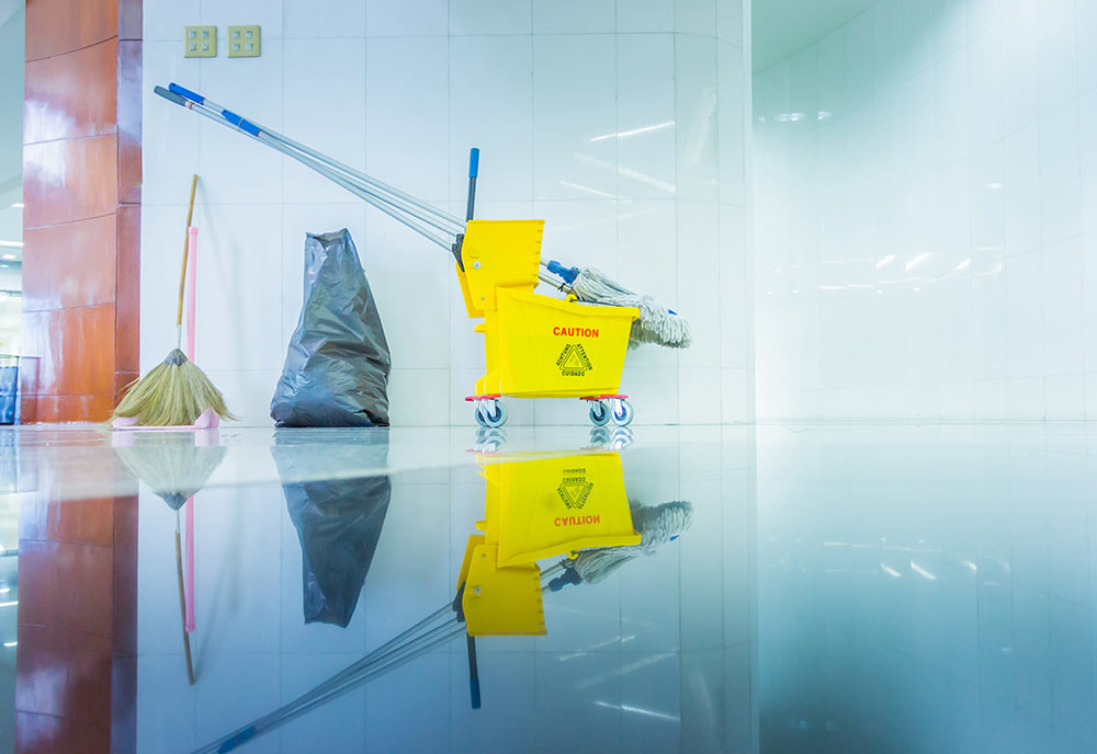 A mop bucket and trash bag shows the signs of a cleaning job finished and well-done.